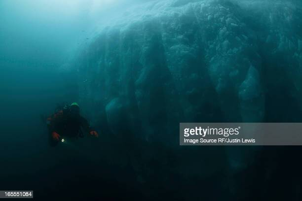 Man scuba diving by glacier