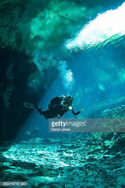 man scuba diving in cenote, underwater view - スキューバダイビング ストックフォトと画像