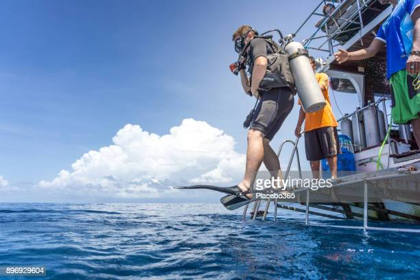 Man Scuba Diving off boat