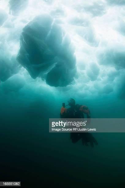 Man scuba diving under glacier