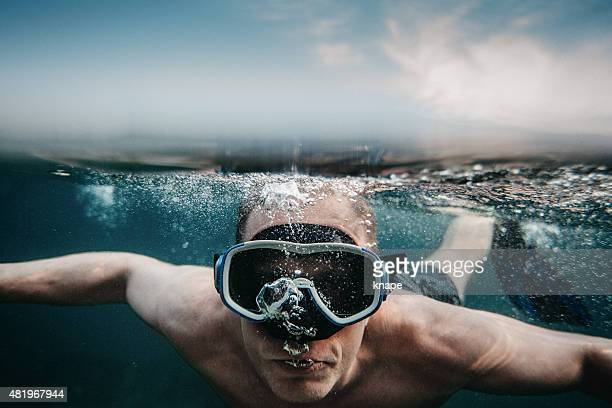 Man scuba diving underwater in sea with mask