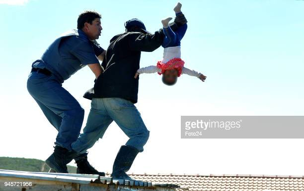 A man scuffles with a police officer as he flings his sixmonthold baby off the roof of a shack at the Joe Slovo informal settlement on April 12 2018...