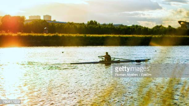 Man Sculling In River During Sunset