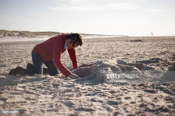 Man sculpting a sand animal on the beach