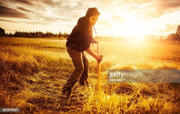 Homme scything herbe sur le champ au coucher du soleil