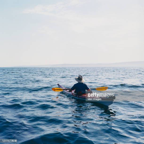 man sea kayaking in puget sound at dusk - sea kayaking stock pictures, royalty-free photos & images