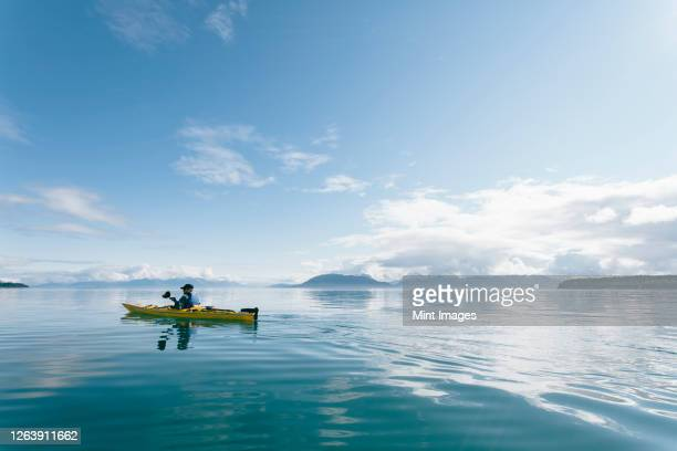 man sea kayaking on sunny day in an inlet on the alaska coastline. - sea kayaking stock pictures, royalty-free photos & images