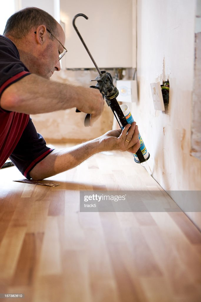 Man sealing the kitchen counter with caulk gun. : Stock Photo