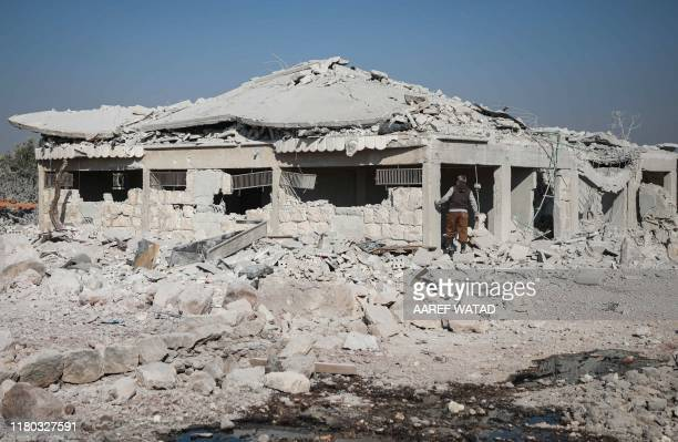 Man searches for survivors in the rubble of a building destroyed by a reported air strike in the Syrian village of al-Sahharah in the countryside...