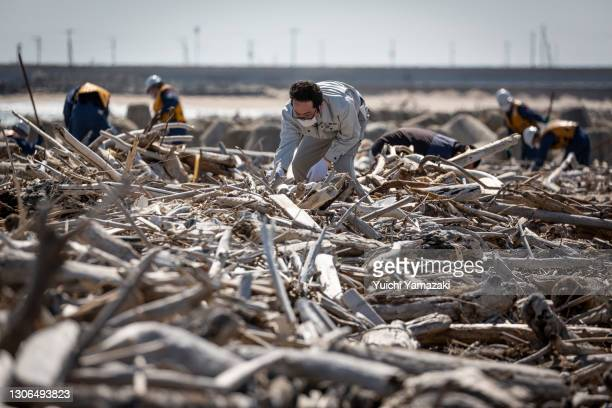 Man searches for the remains of people who went missing after the 2011 earthquake and tsunami on March 11, 2021 in Iwaki, Japan. Japan will today...