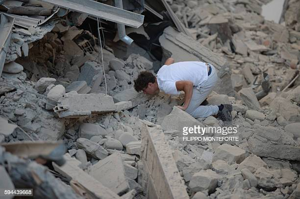 TOPSHOT A man searches for victims among damaged buildings after a strong earthquake hit Amatrice on August 24 2016 Central Italy was struck by a...