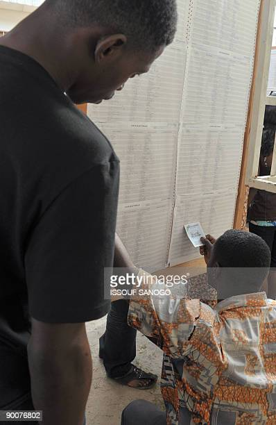 A man searches his name on an electoral list at a registration center in Liberville on August 25 2009 In all 23 candidates have declared themselves...