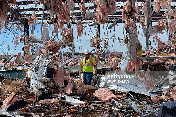 A man searches through a destroyed liquor store on May 21 2013 in Moore Oklahoma Families returned to a blasted moonscape that had been an American...