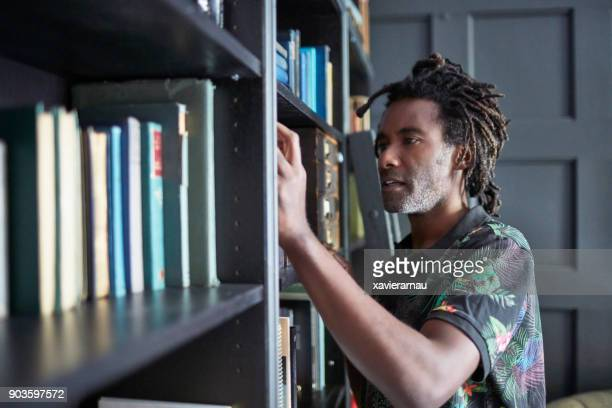 Man searching for book in shelves at home