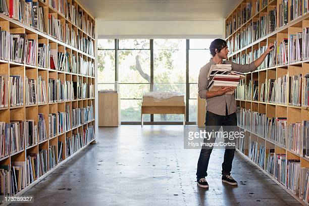 Man searching for books in library