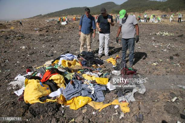 A man searching for personal effects belonging to his brother who was a passenger on ET 302 speaks to a journalist and Recovery worker at the crash...