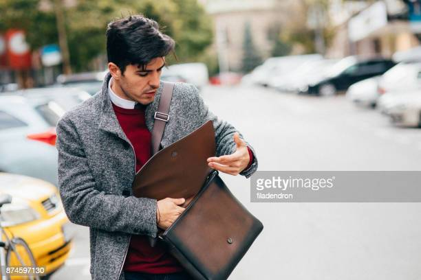 man searching for something in his bag - bag stock photos and pictures