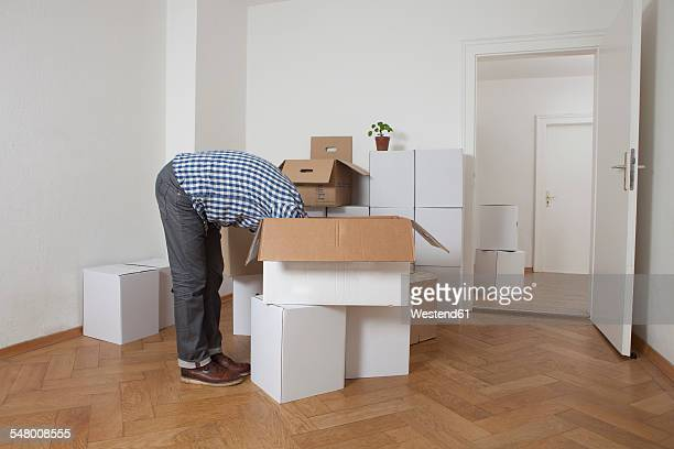 Man searching head first in cardboard box