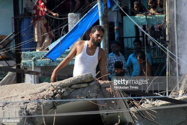 A man searching his family members after building collapse at Nai Basti Bhiwandi on November 24 2017 in Mumbai India Three people were killed and...