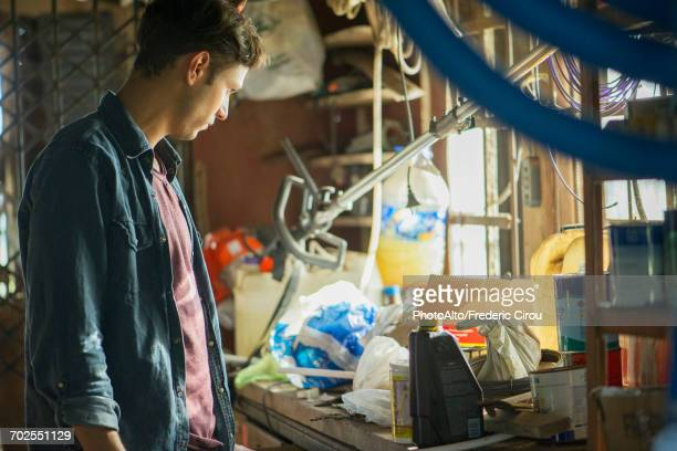 Man searching through cluttered attic for misplaced item