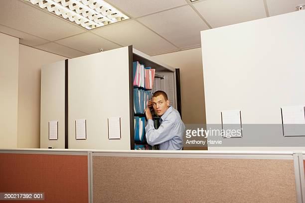 Man searching through office files looking over shoulder