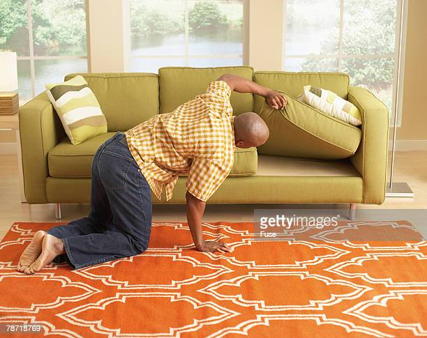 man searching under the couch cushions - cushion stock photos and pictures