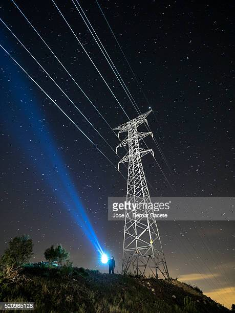 Man searching with a lantern close to a great tower of high tension