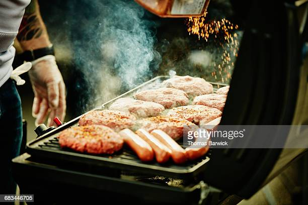 Man seasoning burgers and hot dogs on barbecue