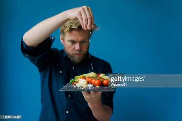 man seasoning platter with cheese and tomatoes - kochen stock-fotos und bilder