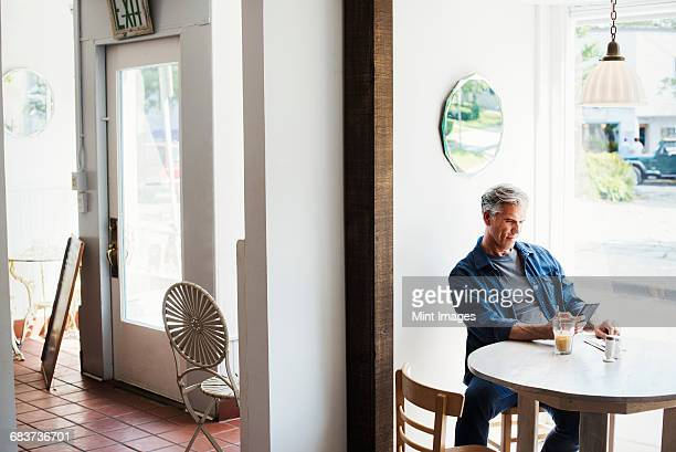 A man seated at a coffee shop table looking at his smart phone.