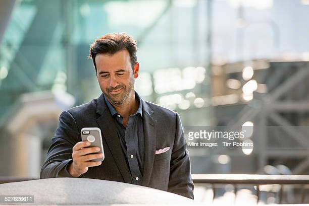 A man seated on a bench checking his smart phone.