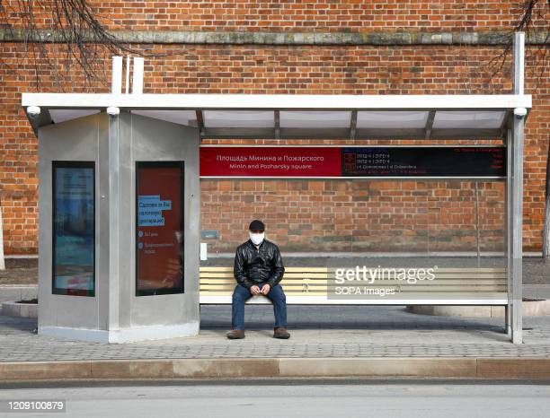 Man seating at a bus stop wearing a face mask as a preventive measure, during the corona virus pandemic. People in Nizhny Novgorod are confined at...