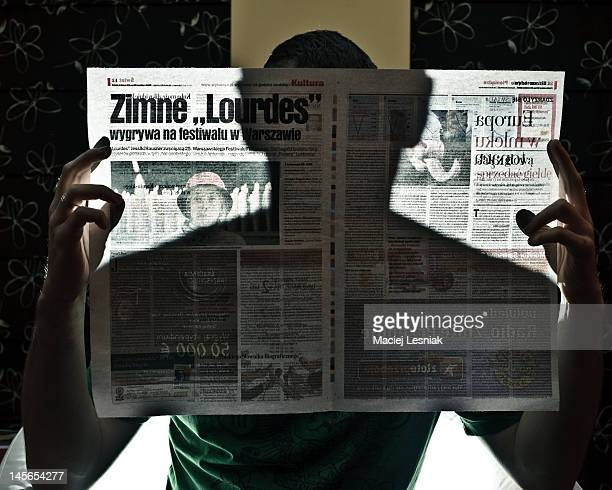 Man seating in an armchair reading a newspaper The shadow of the man can be seen on a newspaper Backlit