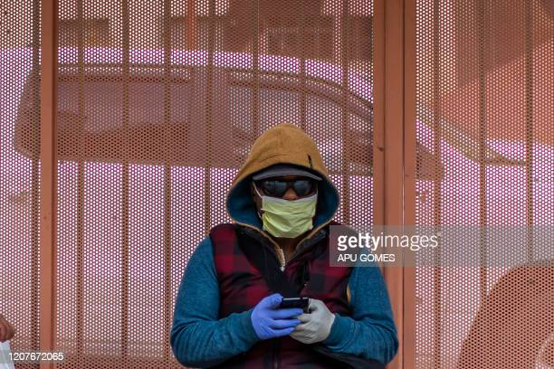 A man seats at a busstop wearing a mask and gloves to protect himself from the Coronavirus in Los Angeles California on March 19 2020 The US...