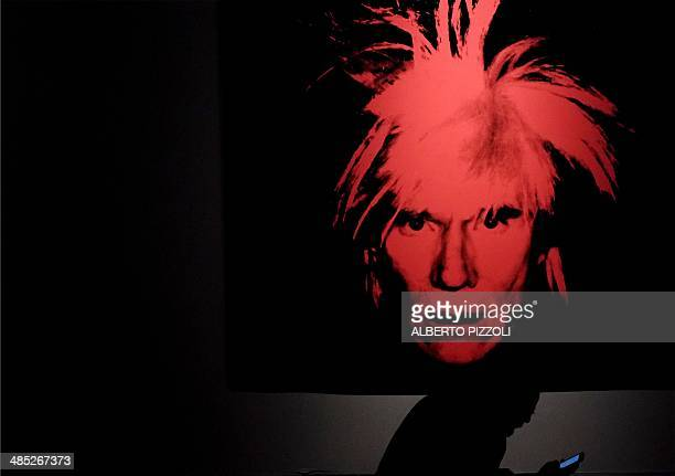 A man seats in front of a selfportrait by US artist Andy Warhol as part of the exhibition 'Warhol' on April 17 2014 in Rome The works of the artist...