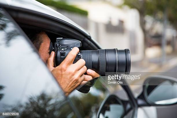 Man secretly taking picture from car window