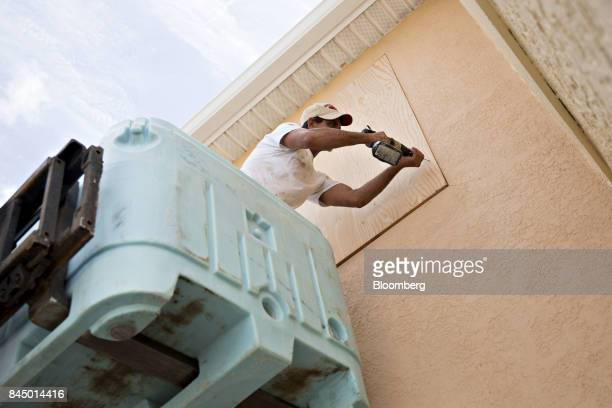 A man secures a piece of plywood over a window ahead of Hurricane Irma in Madeira Beach Florida US on Saturday Sept 9 2017 Hurricane Irma shifted...