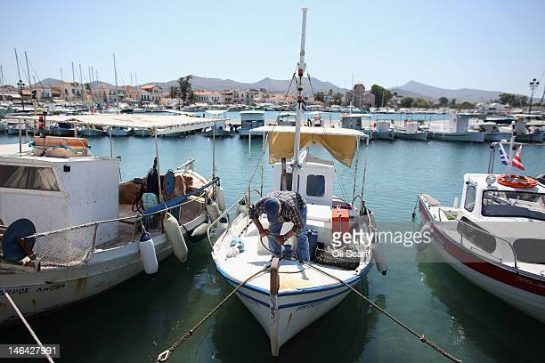 A man secures his boat in the marina on the island of Aegina on June 16 2012 in Aegina Greece The Greek electorate are due to go to the polls...
