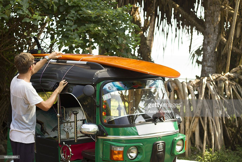 Man secures surfboard on top of tuk tuk : Stock Photo