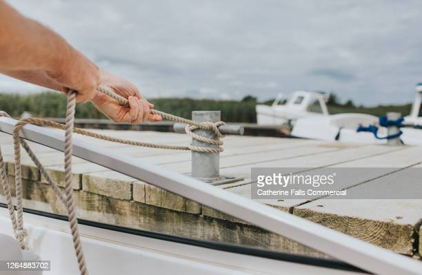 man securing a rope to a boat cleat - west indies stock pictures, royalty-free photos & images