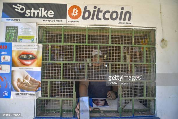 Man seen at a store that accepts bitcoin while holding a cellphone with an application to receive Bitcoin. Salvadoran President Nayib Bukele has...