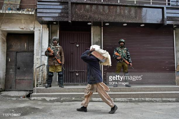 A man seen carrying a load as he walks past paramilitary troopers standing guard during restrictions in Srinagar Indian Kashmir Authorities imposed...