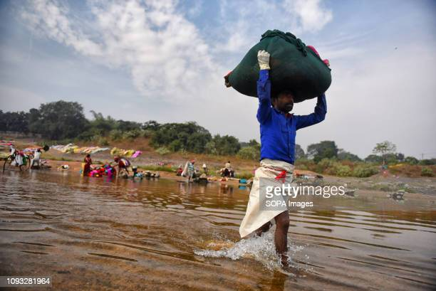 A man seen carrying clothes on his head Dhobi's and their families are directly involve in the washing activities through out the year Almost 1000...