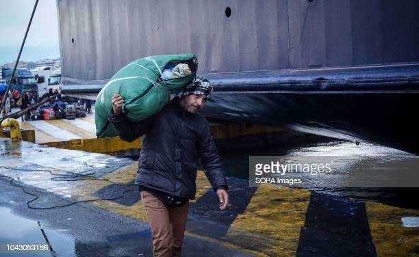 A man seen carrying luggage on his shoulder during his arrival at the port 400 migrants and refugees were transferred upon their arrival from the...