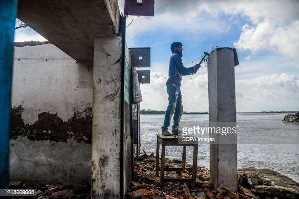 Man seen collecting bricks from a wall that is about to be lost in the river. Thousands of shrimp enclosures have been washed away, while numerous...