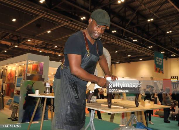 Man seen demonstrating a reuse product during the exhibition. Grand Designs Live exhibition sponsored by Anglian Home Improvements, with more than...