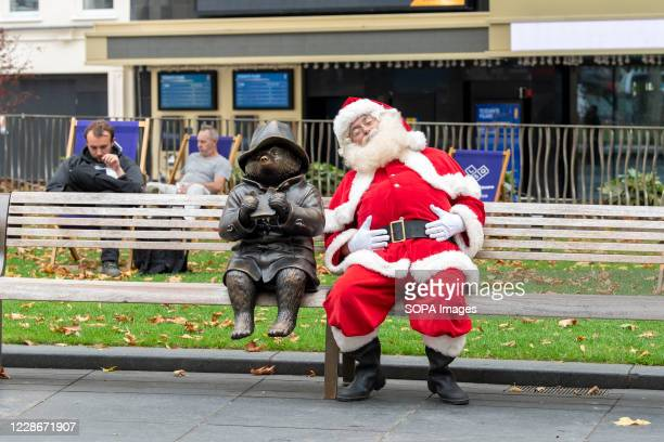 Man seen dressed as Santa Claus seen in Londons Leicester Square on a bench with a statue of Paddington Bear.