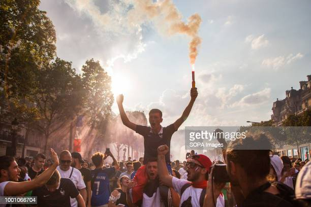 Man seen holding a flare as thousands of supporters gathers at Champs Elysées to receive the world champion French national soccer team. On Saturday...