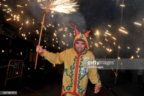 A man seen holding a pyrotechnic fired stick during the Correfocs traditional Catalan holiday and celebrations in Esplugues de Llobregat The...