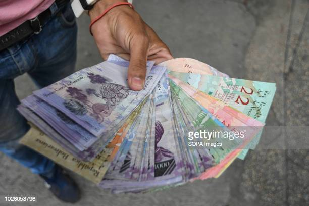 A man seen holding Venezuelan bank notes General strikes against the new currency and the economic measures applied by the Government of Venezuela